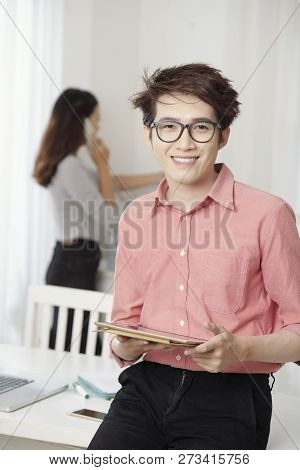 Portrait Of Young Asian Man In Eyeglasses Standing With Touchpad In Modern Office Smiling At Camera