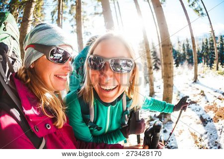 Two Smiling Women In A Winter Hike. Girlfriends With Trekking Poles Are On A Snow Covered Mountain P