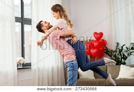 valentines day, love and people concept - happy couple at home
