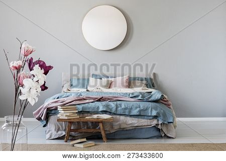 Classy Round Mirror On Grey Wall In Stylish Bedroom Interior With Warm Bed With Blue, Pastel Pink An