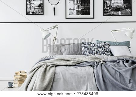 Photo Collector Bedroom With King Size Bed With Grey Bedding And White Lamps, Pile Of Books On The F