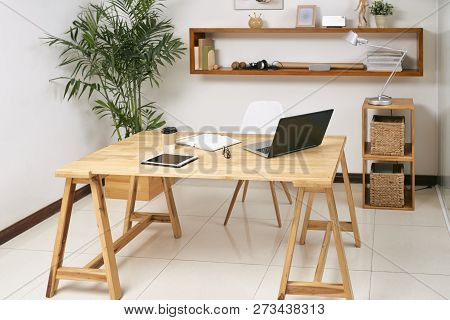 Empty Wooden Office Table With Laptop, Touchpad And Notepad On It With Green Plant And Big Shelf In