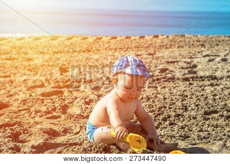 One Year Old Baby Boy Playing On The Beach At The Summer Day Time.