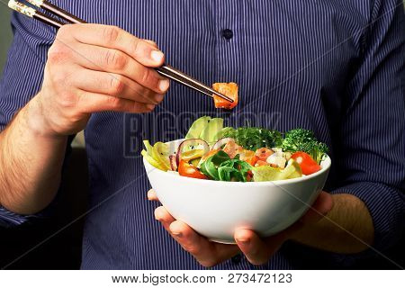 Man In A Shirt Holds Poke Bowl With Salmon, Avocado, Cucumbers, Arugula, Broccoli, Rice, Carrots, An