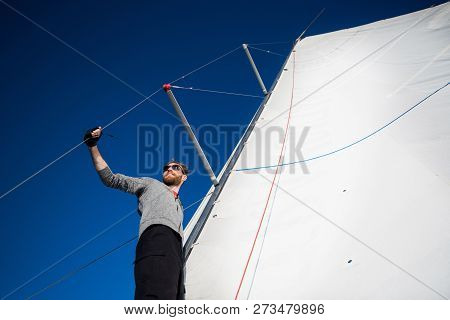 Nice And Confident Young Man Stands On Yacht Board And Look At The Sea Through Glasses. He Is At The
