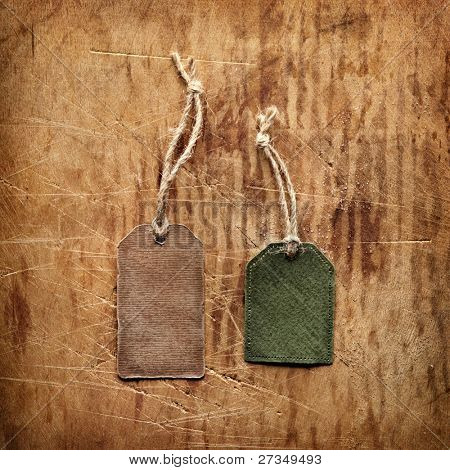 Vintage blank gift tags on old wooden background.