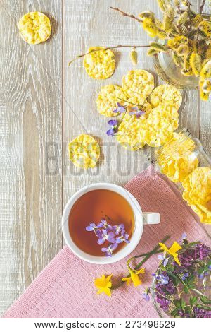 Cup Of Tea With Violet Viola, Delicious Nutritious Cereal Breads And Spring Flowers On Wooden Table.