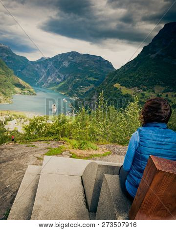 Tourism vacation and travel. Female tourist enjoying beautiful view over magical Geirangerfjorden from Flydalsjuvet viewpoint, Norway. Tourist attraction. poster