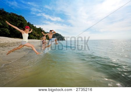Group Of Friends Jumping Into The Sea