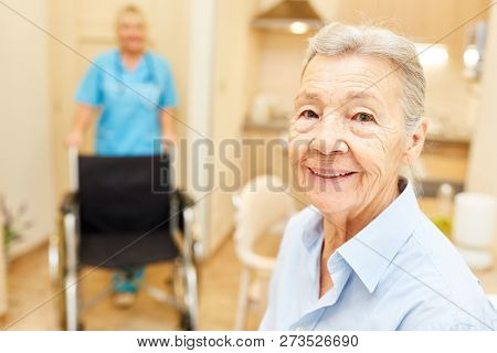 Happy senior woman in her senior citizen home with caregiver and wheelchair