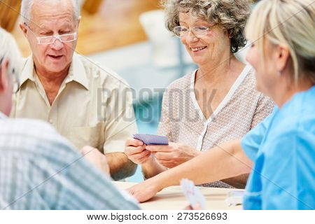 Group seniors and nursing help together at the card game in the retirement home
