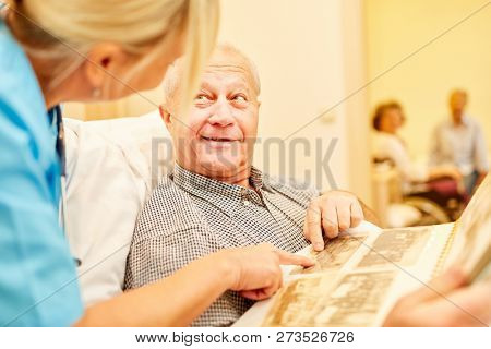 Old man with Alzheimer's looks at photo album supervised by a caregiver