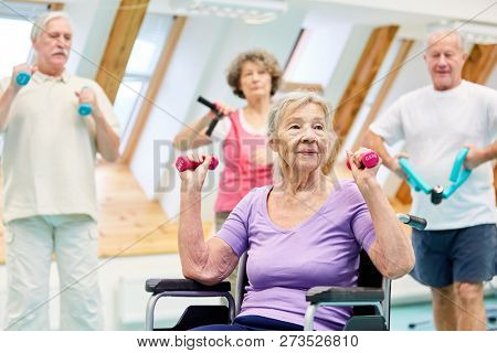 Old woman and seniors group in healthy dumbbell training in senior sport