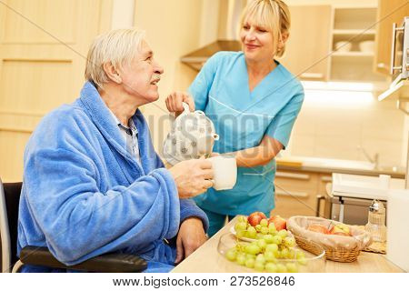 Senior man and caregiver having breakfast with coffee pot in assisted living
