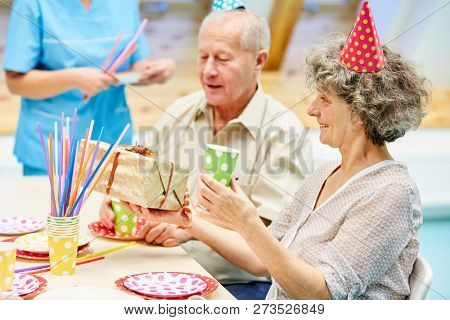 Seniors celebrate a birthday party at the retirement home and unwrap presents