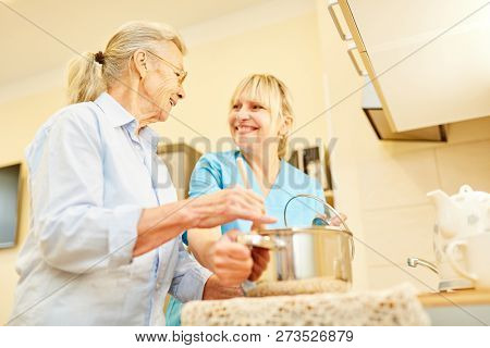 Senior woman and nursing assistant cook together in the kitchen in assisted living