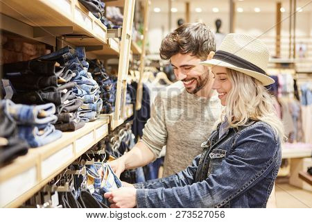 Young couple shopping in front of the jeans selection in fashion shop in shopping mall
