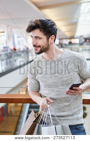 Young man uses a smartphone shopping app for price comparison