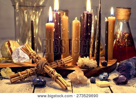 Burning Candles, Old Bottles And Flasks, Crystals And Cross On Table. Magic Ritual. Wicca, Esoteric