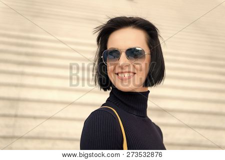 Girl With Brunette Hair Smile In Black Clothes. Woman In Sunglasses On Stairs. Fashion And Accessory