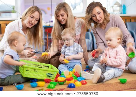 Group Of Children 1-2 Years Old Playing In Kindergarten Or Daycare Centre Under The Supervision Of M