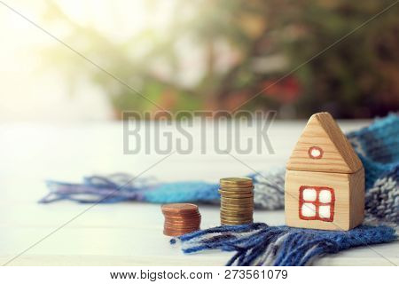Stack Of Coins And A Wooden House On The Background Of A Scarf And Blurry Outlines Of A Christmas Tr