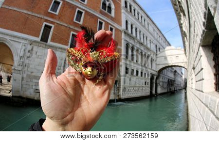 Hand With The Small Mask And In The Background The Bridge Of Sighs In Venice In Italy