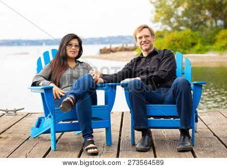 Multiracial Couple, Caucasian Man And Asian Woman, Sitting On Blue Adirondack Chairs On Wooden Pier
