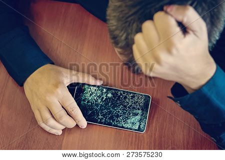 Desperate And Astonished Man Holds Cracked Smartphone . Screen Broken Smartphone. Cracked Phone Brok