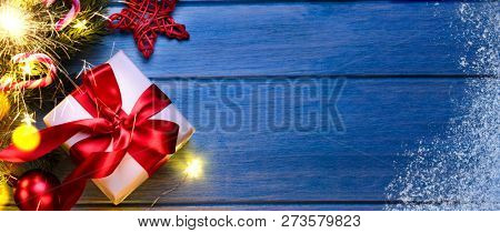 Christmas or New Year gift with sparkler and festive fir tree on blue table at night