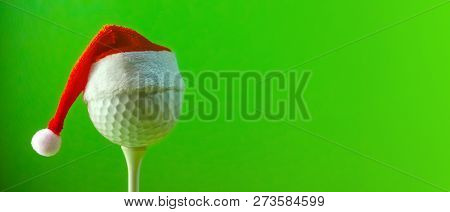 A Red Santa Claus Hat Is Worn On A Golf Ball Mounted On A Tee. A Long Banner With Copy Space On The