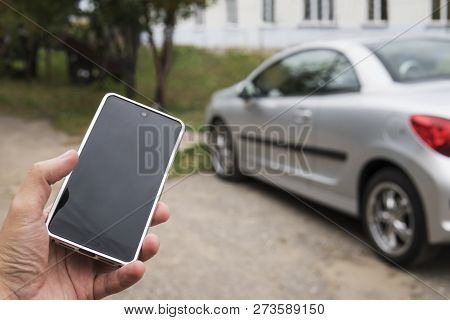 Mobile Phone Apps For Car Owners Concept. Man Using Smart Phone To Check Status, Control His New Car