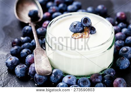 Serving Of Yogurt With Whole Fresh Blueberries And Oatmeal On Old Rustic Table