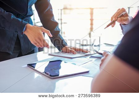 Business People Examining Financial Reports Working On Desk And Analyzing Business Growth On Tablet.
