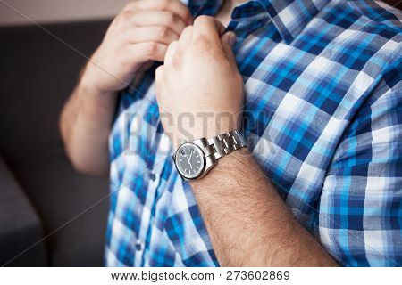sturdy man in a blue plaid shirt with a short sleeve and a watch on his wrist buttons collar poster