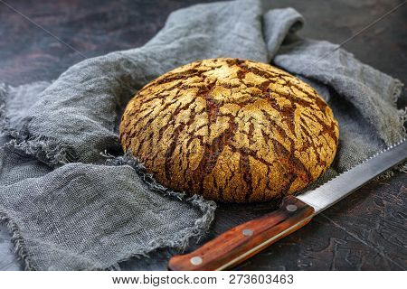 Loaf of rye artisanal bread on a dark textured table with linen cloth, selective focus. poster
