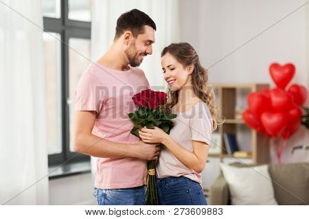 valentines day, relationships and people concept - happy couple with bunch of flowers hugging at home