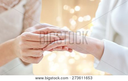 gay, homosexuality, same-sex marriage and lgbt concept - close up of lesbian couple hands putting on wedding ring over festive lights background