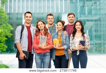 education, high school and people concept - group of smiling students with books over university background