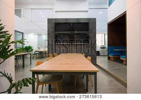 Plasma Displays Hanging On Granite Wall In Coworking Space Of Modern Office. Long Wooden Table And C