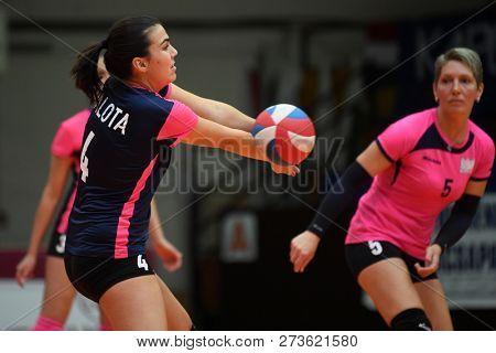 KAPOSVAR, HUNGARY – DECEMBER 2, 2018: Gabriella Benedek (with ball) in action at a Hungarian National Championship volleyball game between Kaposvar (white) and Palota VSN (blue) in Sportcsarnok Kaposv