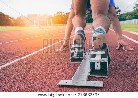 Sport.back View Of Men's Feet On Starting Block Ready For A Sprint Start.