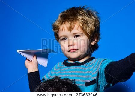 Cute Boy Is Flying Paper Aircraft. Little Child Holds Paper Airplane In Hand Dreaming About Being Pi