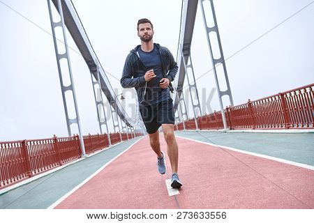 Morning Workout. Full Length Rear View Of Young Man In Sports Clothing Exercising While Jogging On T