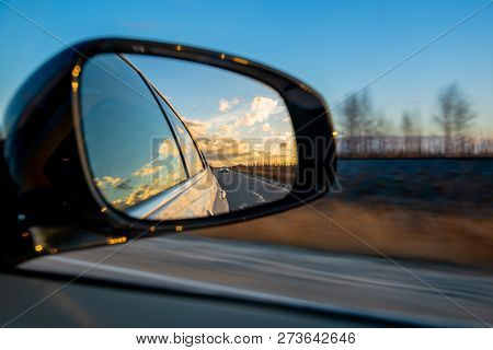 Driving A Car On An Autumn Road With Clouds In The Rear View Mirror