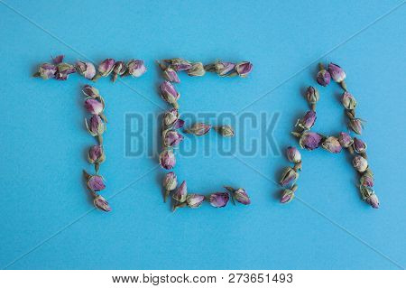 Word Tea Made From Dried Rose Buds. Rose Tea On Blue Background. Food Lettering