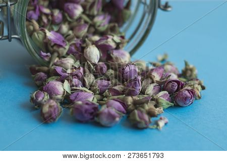 Dried Rose Buds And Jar For Tea Storage On Blue Background