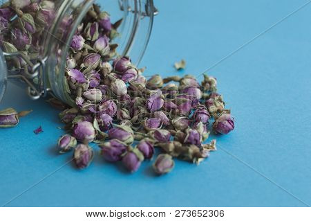 Herbal Tea In A Glass Jar. Dried Rose Buds On Blue Background