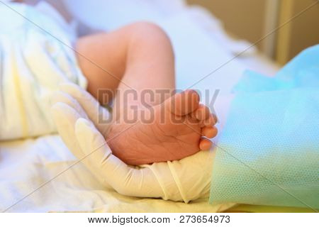 Doctor Holding Newborn Child's Foot In Hospital, Closeup