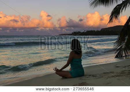 Woman Practicing Yoga In Sunset On The Beach. Healthy People Lifestyle. Yoga In Sunset On The Beach.